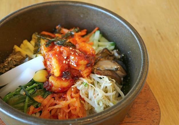 Bibimbap lub koreański tradycyjny mieszany ryż z mięsem i bukietem warzyw w gorącej kamiennej misce