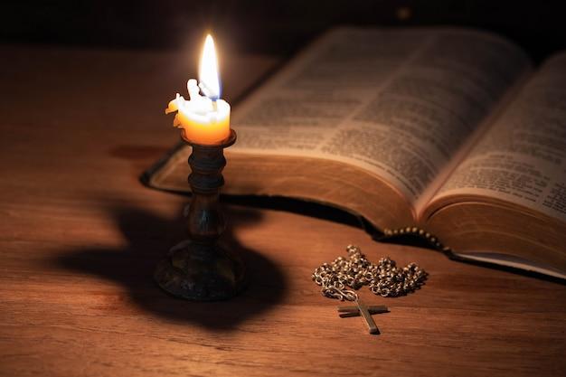 Biblia, drewniany krzyż i świece