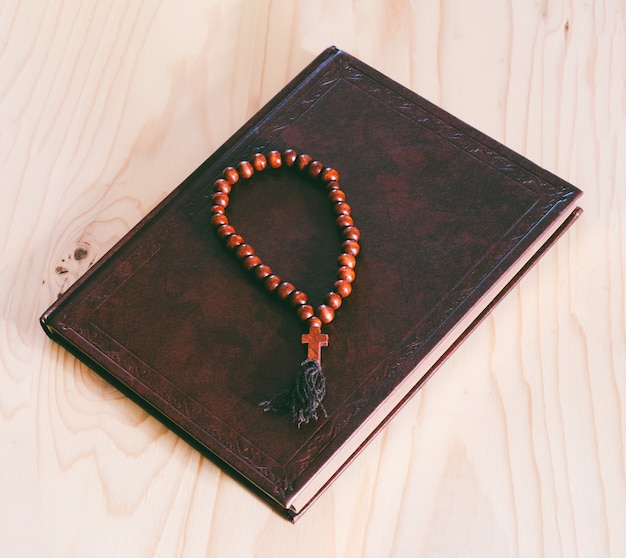 Biblia i drewniany różaniec na stole, odgórnego widoku zbliżenie