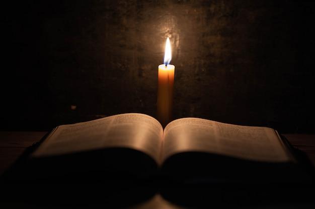 Biblia i świeca na starym dębowym drewnianym stole.