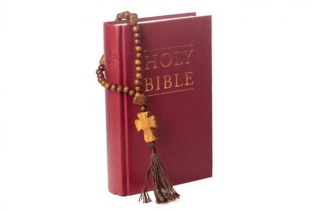 Biblia na białym. święta księga i drewniany różaniec.