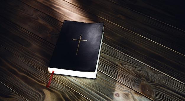 Biblia na drewnianym stole. książka z krzyżem religii chrześcijańskiej