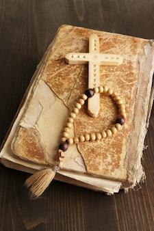 Biblia, różaniec i krzyż na drewnianym stole z bliska