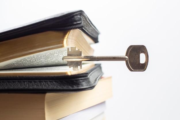 Biblia z kluczem i otwartą książką. metafora klucz do poznania, mądrości i wiedzy