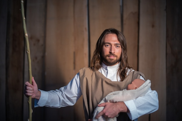 Biblijna postać józefa trzymającego dziecko jezusa w łóżeczku