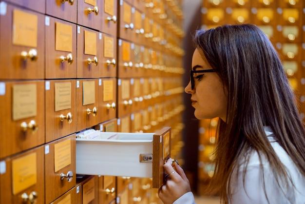 Bibliotekowy lub archiwalny katalog kart referencyjnych. studencka dziewczyna próbuje znaleźć potrzebną książkę przy użyciu papierowej bazy danych biblioteki