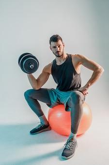 Biceps treningowy sportowca z hantlami na piłce fitness. przekonany, młody brodaty mężczyzna europejski nosić mundur sportowy i patrząc na kamery. na białym tle na turkusowym tle. sesja studyjna