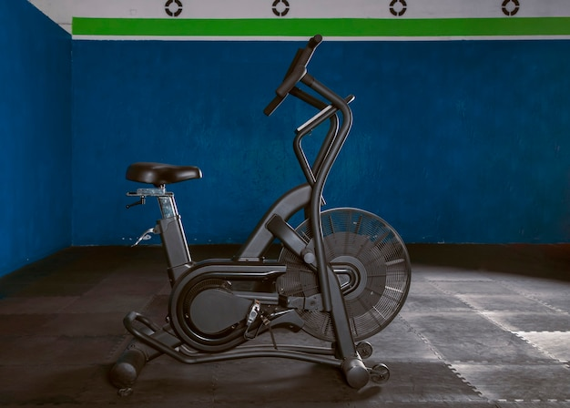 Bicicleta de aire en gimnasio con piso de goma y fondo azul