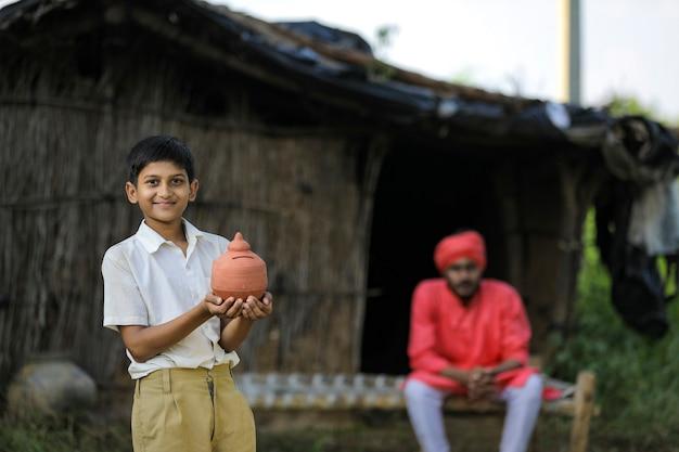 Biedne dziecko rolnika, trzymając w ręku gliniane skarbonki z rolnikiem w domu