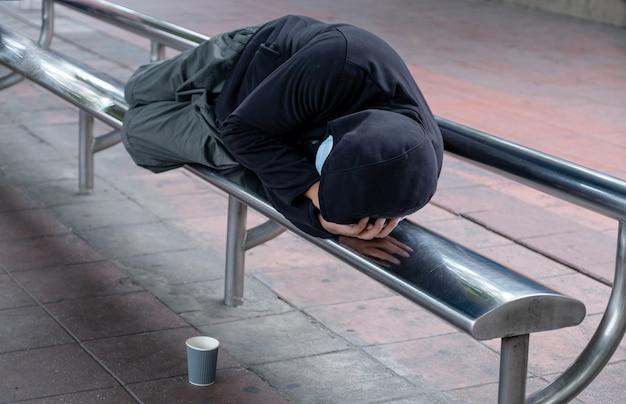 Biedny bezdomny śpi na krześle przystanku autobusowego był tam kubek do postawienia żebraka, ponieważ bieda prosiła o pomoc ludzi przechodzących na ulicach.