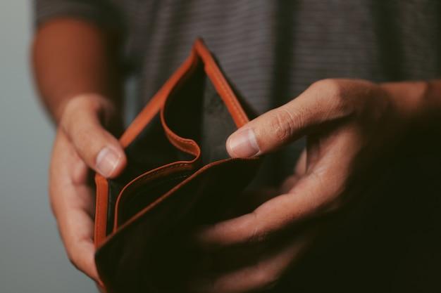 Biedny człowiek otwiera pusty portfel szukający pieniędzy, spłukany, zbankrutowany koncepcja