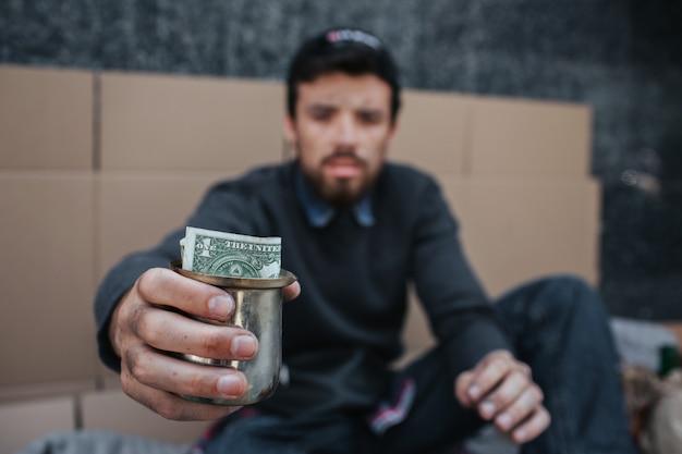 Biedny i brudny człowiek siedzi na ziemi i prosi o pieniądze
