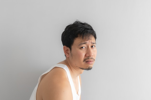 Biedny i przygnębiony mężczyzna nosić biały podkoszulek na szarym tle. pojęcie rozpaczliwego życia.