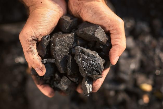 Biedny mężczyzna w średnim wieku trzymający ręce kamiennego węgla na sprzedaż, aby zapewnić żywność dla swojej rodziny
