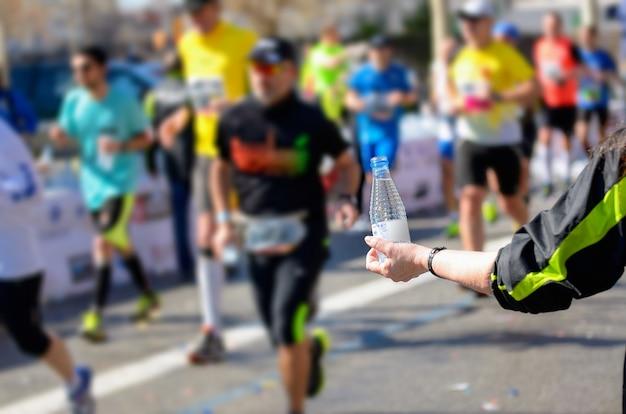 Bieg maratoński, biegacze na drodze, ochotnik podający wodę w punkcie gastronomicznym
