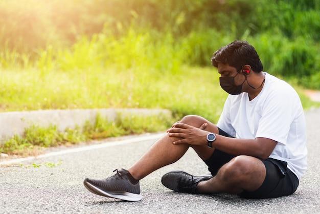 Biegacz czarny człowiek nosić zegarek siedzący, podczas biegania używa wspólnego trzymania rąk na kolanie