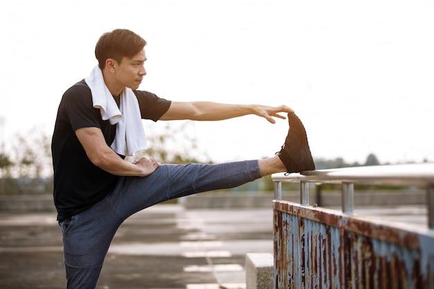 Biegacz człowiek robi ćwiczenia rozciągające, przygotowując się do wieczornego treningu w parku słońca.