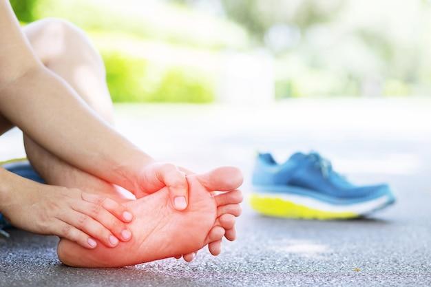 Biegacz dotyka bolesnego skręcenia lub złamania kostki. wypadek podczas treningu biegacza sportowca.