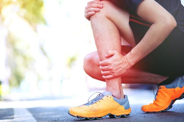 Biegacz dotyka bolesnego skręcenia lub złamania kostki