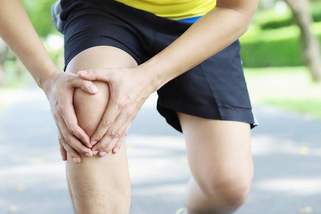 Biegacz dotyka bolesnej skręconej lub złamanej kostki.