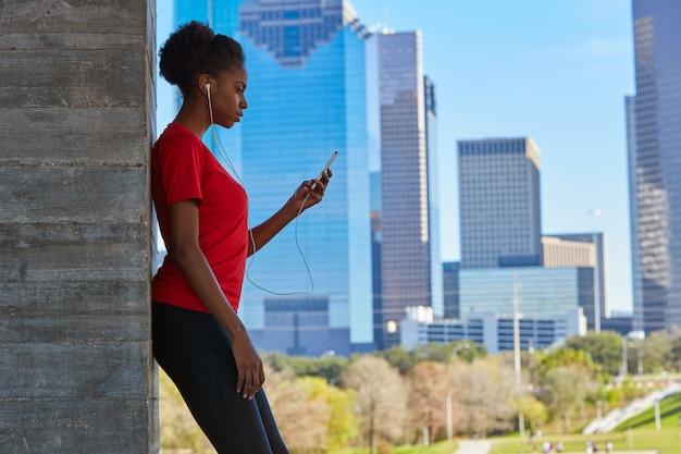 Biegacz dziewczyna słucha muzyczne słuchawki w mieście