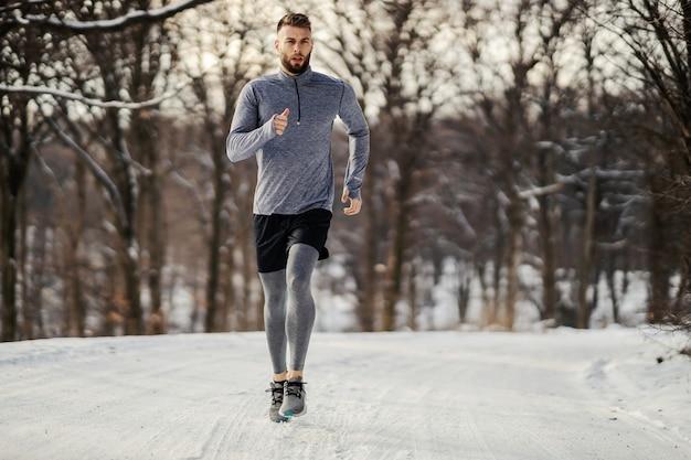 Biegacz jogging w przyrodzie w zimie na śnieżną pogodę.