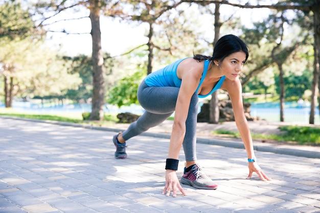Biegacz kobieta fitness w pozycji początkowej