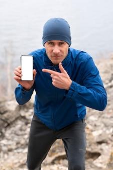 Biegacz mężczyzna pokazuje pusty telefon w przyrodzie