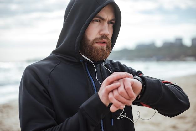 Biegacz na kapturze odnotowuje czas na plaży
