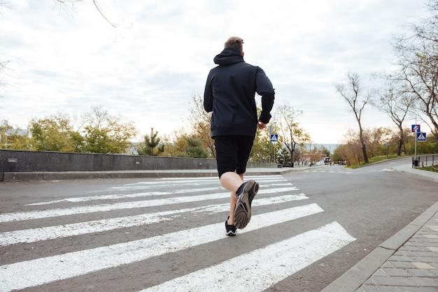 Biegacz na przejściu dla pieszych widok z tyłu