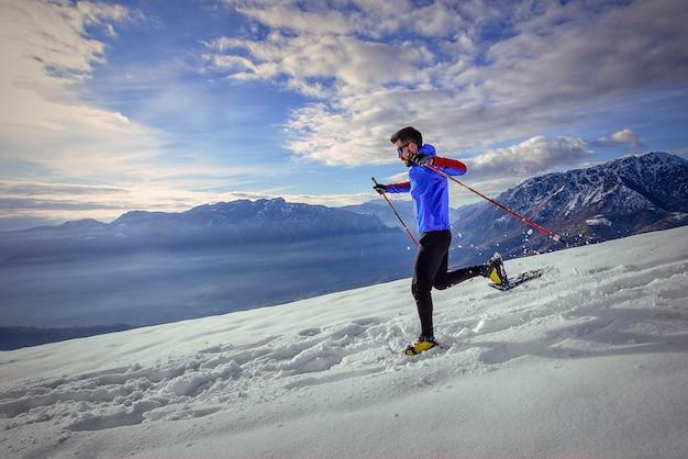 Biegacz na śniegu w rakietach śnieżnych zjazdowych