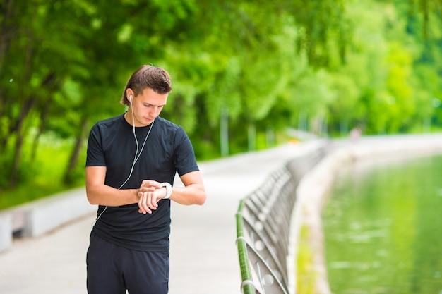 Biegacz patrząc na inteligentny zegarek pulsometr z przerwą podczas biegu