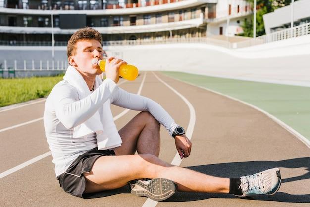 Biegacz pije napój energetyczny