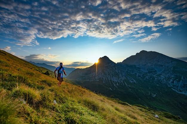 Biegacz skyrunner biegnie w górach, gdy wschodzi słońce