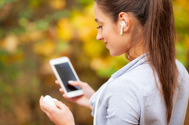 Biegacz słucha muzyki. fitness, sport i zdrowy styl życia - uśmiechnięty biegacz ze słuchawkami