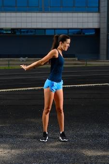 Biegacz sportowiec działa na torze lekkoatletycznym, trenując jej cardio. kobieta jogging na wyścig konkurencji na letnim stadionie.
