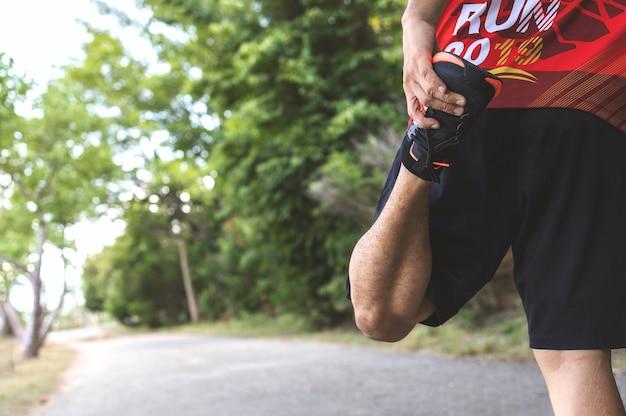 Biegacz-sportowiec rozgrzewa swoje ciało przed rozpoczęciem biegania po roadparku z miękkim ogniskiem