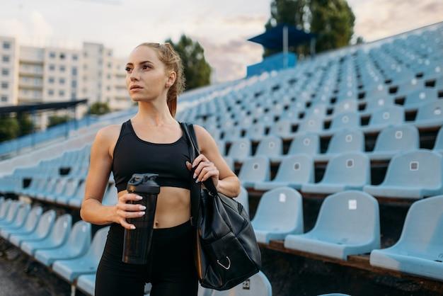 Biegacz w odzieży sportowej na trybunie, trening na stadionie. kobieta robi ćwiczenia rozciągające przed bieganiem na arenie na świeżym powietrzu