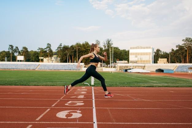 Biegacz w odzieży sportowej przekracza linię mety, trenując na stadionie. kobieta robi ćwiczenia rozciągające przed bieganiem na arenie na świeżym powietrzu