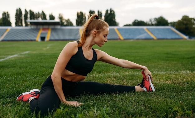 Biegacz w odzieży sportowej, trening na stadionie. kobieta robi ćwiczenia rozciągające przed bieganiem na arenie na świeżym powietrzu