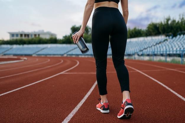 Biegacz w odzieży sportowej, widok z tyłu, trening na stadionie. kobieta robi ćwiczenia rozciągające przed bieganiem na arenie na świeżym powietrzu