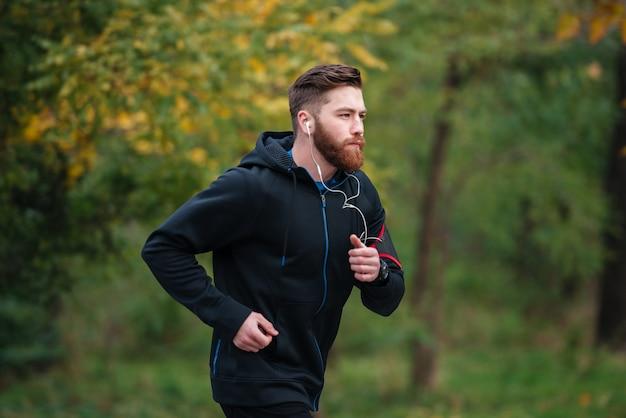 Biegacz w widoku z boku parku w ciepłych ubraniach