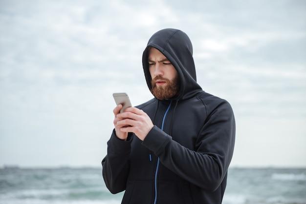 Biegacz z telefonem na plaży patrzący na telefon