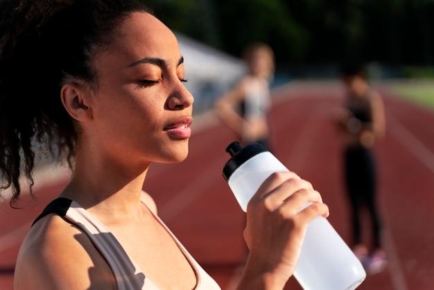 Biegacz z widokiem z boku trzymający butelkę wody