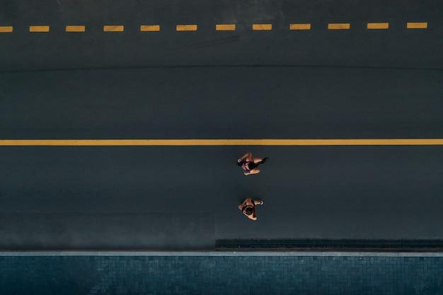 Biegacze biegaczy fitness. zdrowy, aktywny tryb życia. aktywne dziewczyny biegające razem na widok drogi z góry.