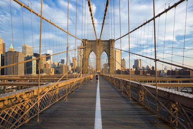 Biegacze dojeżdżający na manhattan przez most brookliński. nowy jork, usa