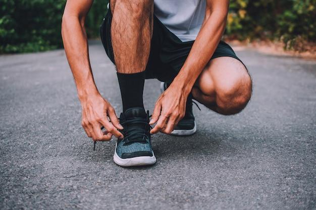 Biegacze przywiązani w butach, mężczyzna biegający po ulicy biegają do ćwiczeń, biegają w tle sportowym i zbliżają się do butów