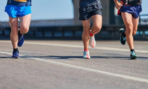 Biegacze. sportowi mężczyźni biegający w odzieży sportowej na miejskiej drodze