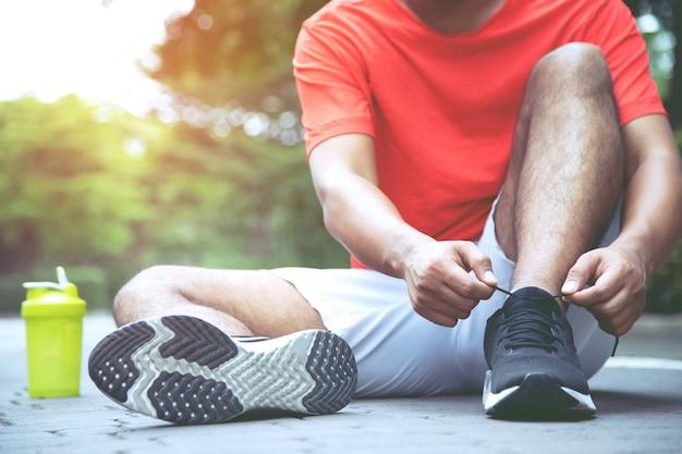 Biegacze wiążą buty w parku