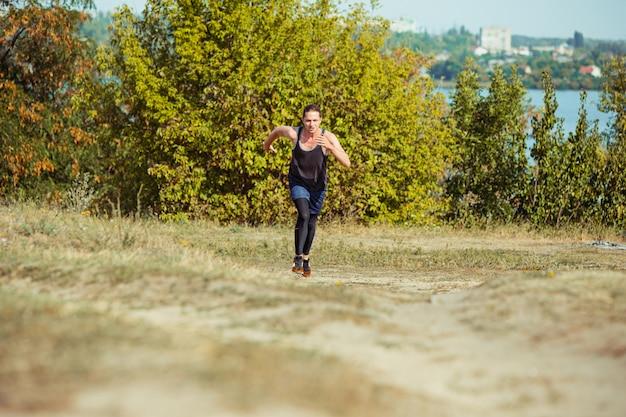 Bieganie. biegacz mężczyzna sprint na świeżym powietrzu w malowniczej przyrodzie. dopasowany, muskularny mężczyzna sportowiec szlak treningowy do biegu maratońskiego. sportowy sprawny atletyczny mężczyzna w odzieży kompresyjnej w sprincie